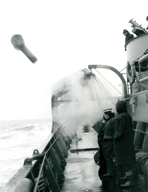 A depth charge and its carrier leave HMCS Pictou. [PHOTO: LIBRARY AND ARCHIVES CANADA—PA116838]