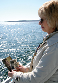 Susan Clark looks at photos of her father while on board HMCS Sackville. Her father's ashes were later committed to the sea. [PHOTO: DAN BLACK]