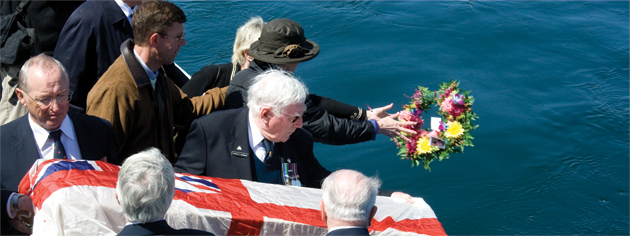 A burial board covered with the White Ensign is used to commit a sailor's ashes to sea on board HMCS Sackville. [PHOTO: DAN BLACK]