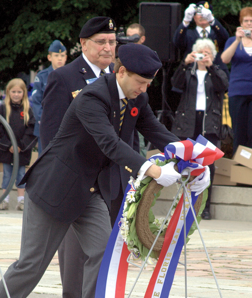 The prince, assisted by First Vice Wilf Edmond, places a wreath. [PHOTO: ADAM DAY]