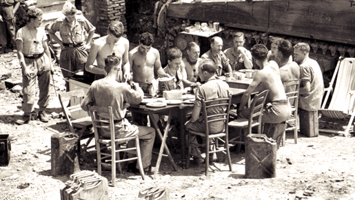 Members of the Ontario Regt. dine in Italy, June 1944. [PHOTO: BARRY G. GILROY, LIBRARY AND ARCHIVES CANADA—PA145776]