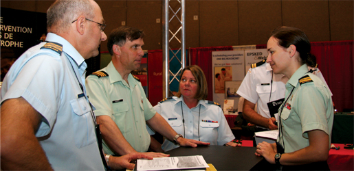 From left: Maj. Alain Gagnon, Lt.-Col. Randy Russell, Capt. Anne Johnston and Maj. Annette Snow participate in a planning session in the Canadian Forces recruitment booth at an emergency physicians' convention. [PHOTO: SHARON ADAMS]