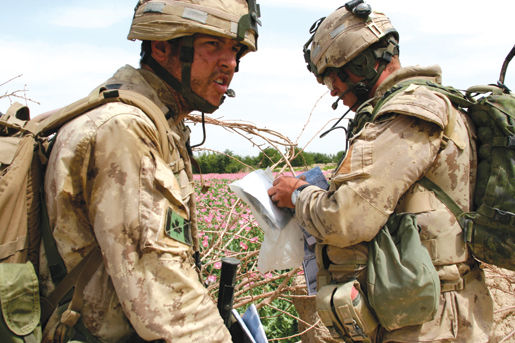 Capt. Bob Barker (left) stops the patrol as another Bravo Company soldier checks the map. [PHOTO: ADAM DAY]