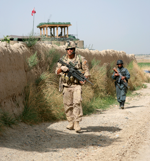 A Bravo Company soldier and an Afghan policeman leave Haji for a patrol. [PHOTO: ADAM DAY]
