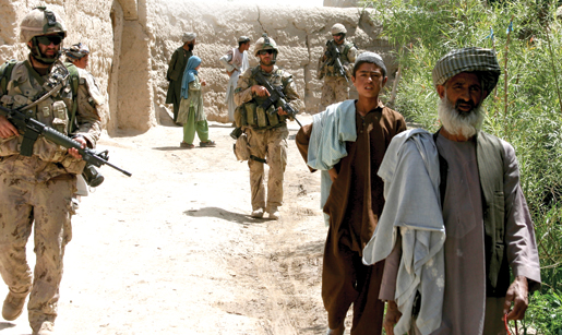 Villagers and Bravo Company soldiers walk together near Haji. [PHOTO: ADAM DAY]