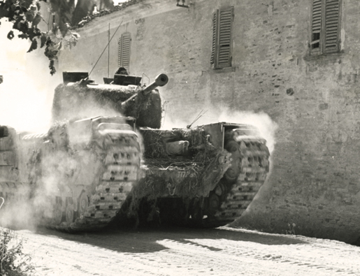 A tank kicks up dust as it moves through an Italian town during the assault on the Gothic Line. [PHOTO: LIBRARY AND ARCHIVES CANADA—PA185004]