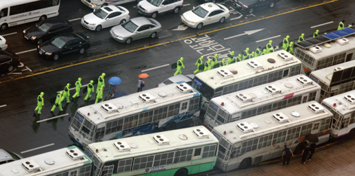 South Korean riot police in rain gear rush to meet protesters in Seoul. [PHOTO: TOM MACGREGOR]