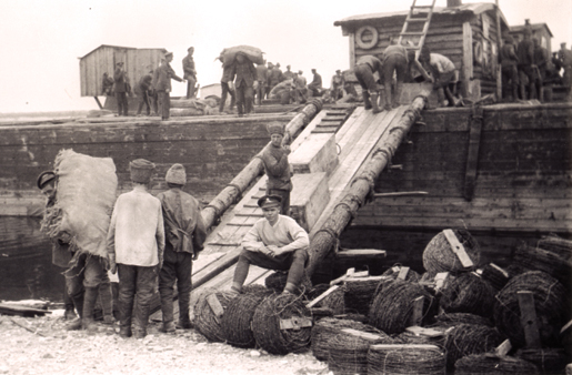 A Canadian gunner (seated) supervises prisoners as they load a barge at Yemetskoe, Northern Russia, in May 1919. [PHOTO: ALAN A. OUTRAM, LIBRARY AND ARCHIVES CANADA—PA037404]