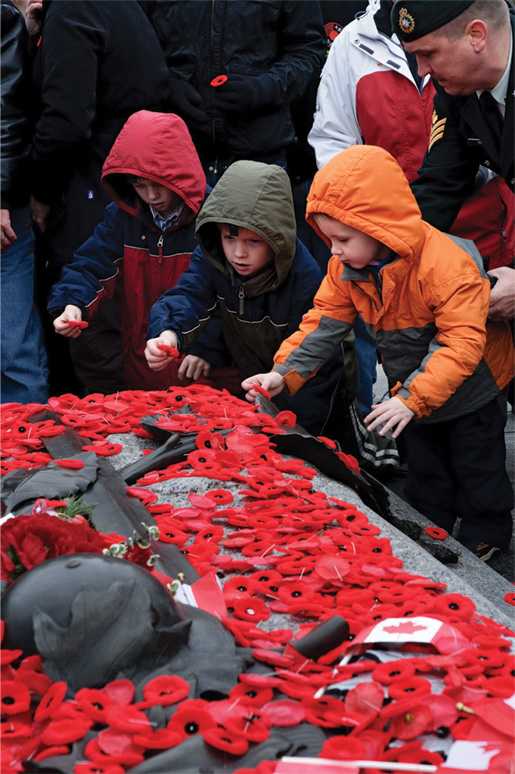 Children place their poppies on the Tomb of the Unknown Soldier. [PHOTO: METROPOLIS STUDIO]