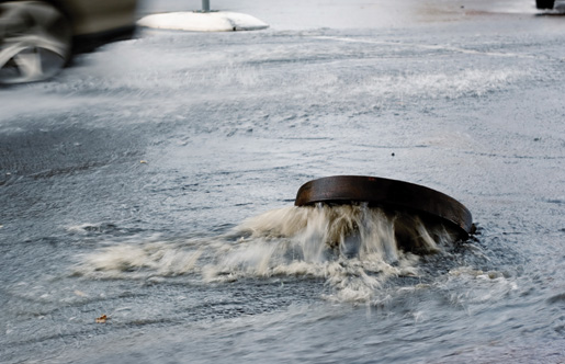 A storm sewer blows its cover during a rainstorm. [PHOTO: ©iStockphoto/Dizzy]