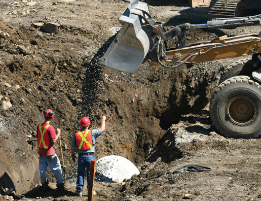 Workers help install a concrete pipe. [PHOTO: ©iStockphoto/kozmoat98]