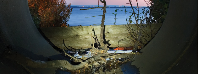 Debris collects at the mouth of a storm drain along the St. Lawrence River. [PHOTO: ANDREW EMOND, WWW.WORKSONGS.COM]
