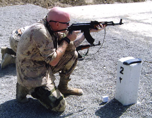 Doyle test fires an AK-47 in Kabul in 2004. [PHOTO: COURTESY NICOLE DOYLE]