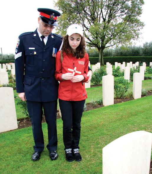 Police Staff Sergeant Nick Lisi and daughter Victoria say a few words at the grave of Pte. Emile Comeau. [PHOTO: DAN BLACK]