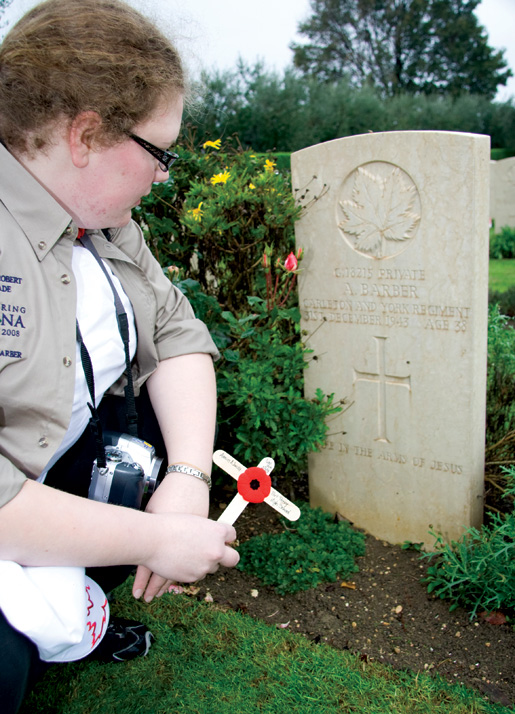 Amie Nault places a cross in front of the grave of Pte. Albert Barber. [PHOTO: DAN BLACK]