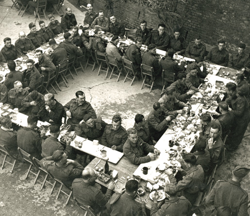 Members of the Seaforth Highlanders sit down for their Christmas dinner. [PHOTO: TERRY ROWE, LIBRARY AND ARCHIVES CANADA–PA152839]