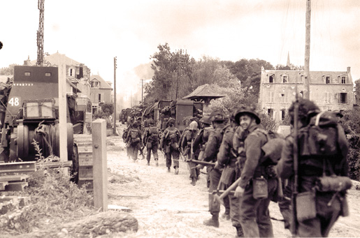 Canadian soldiers and vehicles move through a village near the Normandy coast, June 6, 1944. [PHOTO: LT. FRANK L. DUBERVILL, LIBRARY AND ARCHIVES CANADA–PA131436]