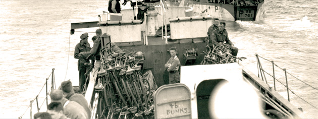 Landing craft en route to Normandy, June 6, 1944. Note the stack of bicycles and the number on the door telling how many bunks are below. [PHOTO: GILBERT ALEXANDER MILNE, LIBRARY AND ARCHIVES CANADA–PA135966]