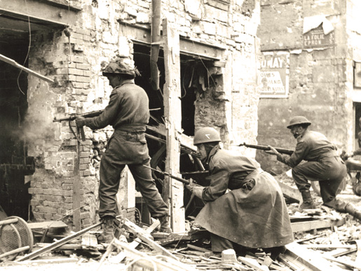 A Canadian soldier fires on the enemy in a house in Caen, July 10, 1944. [PHOTO: KEN BELL, LIBRARY AND ARCHIVES CANADA–PA132727]