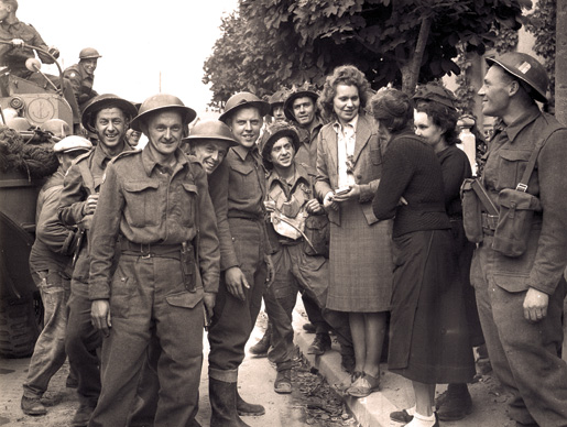 French women greet Canadian soldiers in a liberated town, June 10, 1944. [PHOTO: LT. DONALD I. GRANT, LIBRARY AND ARCHIVES CANADA–PA137978]