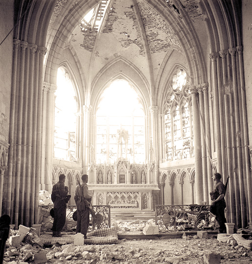 Unidentified Canadian infantry visit a bomb-damaged church in Carpiquet, near Caen, July 12, 1944. [PHOTO: KEN BELL, LIBRARY AND ARCHIVES CANADA–PA162545]