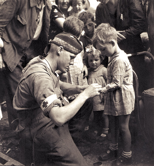 Canadian Private G.R. MacDonald gives first aid to an injured boy. [PHOTO: KEN BELL, LIBRARY AND ARCHIVES CANADA–PA135956]