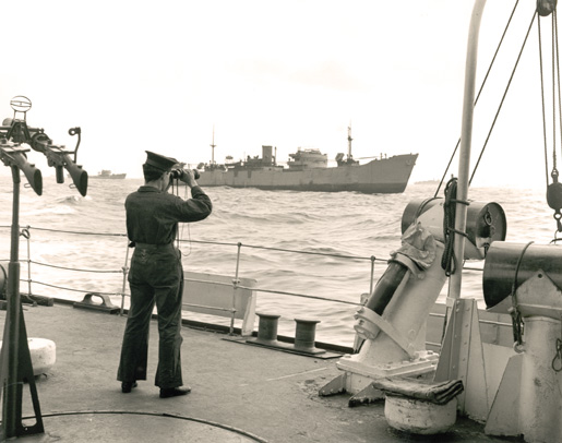 A sailor in HMCS Skeena studies the waters around an unidentified Liberty ship in 1943. [PHOTO: GERALD THOMAS RICHARDSON, LIBRARY AND ARCHIVES CANADA—PA166889]