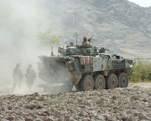 A LAV III provides perimeter security for soldiers on patrol. [PHOTO: SERGEANT LOU PENNEY, CANADIAN FORCES]