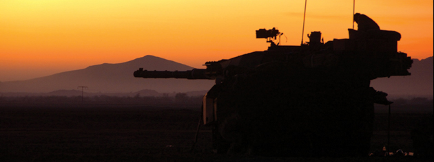 An orange sky and the mountainous terrain of Afghanistan provide a backdrop for a military vehicle. [PHOTO: COMBATCAMERA/DND]
