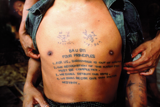 The tattooed chest of a young Karen fighter spells out his fight for freedom and democracy against a suppressive government in Burma (Myanmar). [PHOTO: ROBERT SEMENIUK]