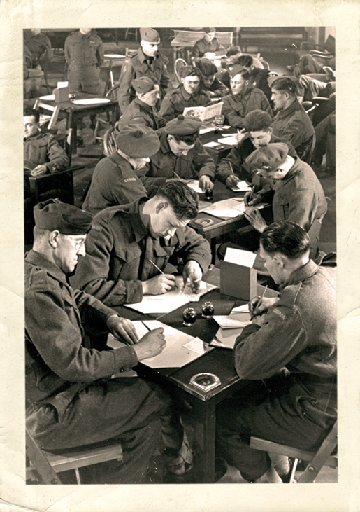 Soldiers take advantage of  the writing facilities inside a Canadian Legion recreation hut in England. [PHOTO: A. LOUIS JARCHE]