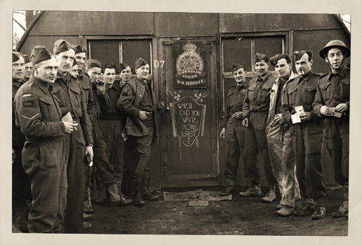 Soldiers stand next to a Canadian Legion War Services sign encouraging soldiers to write home. [PHOTO: A. LOUIS JARCHE]