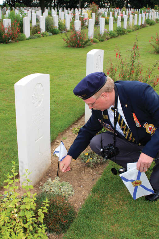 David Andrews places a provincial flag on the grave of a fellow Nova Scotian at Beny-sur-Mer Canadian War Cemetery in Normandy. [PHOTO: SHARON ADAMS]