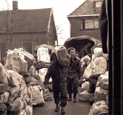 Members of the Pioneer Corps unload Christmas mail at 2 Canadian Corps Army Post Office in  the Netherlands, December 1944. [PHOTO: B.J. GLOSTER, LIBRARY AND ARCHIVES CANADA—PA137637]