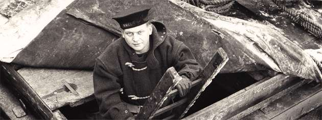 A member of the RCN Naval Control of Shipping Service emerges from a ship's hold after examining the cargo. [PHOTO: LIBRARY AND ARCHIVES CANADA—PA104427]