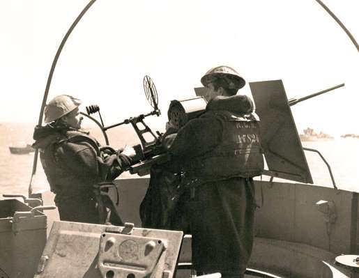 Personnel aboard HMCS Prince Henry man a gun off the coast of France, June 1944. [PHOTO: DENNIS SULLIVAN, LIBRARY AND ARCHIVES CANADA—PA132793]