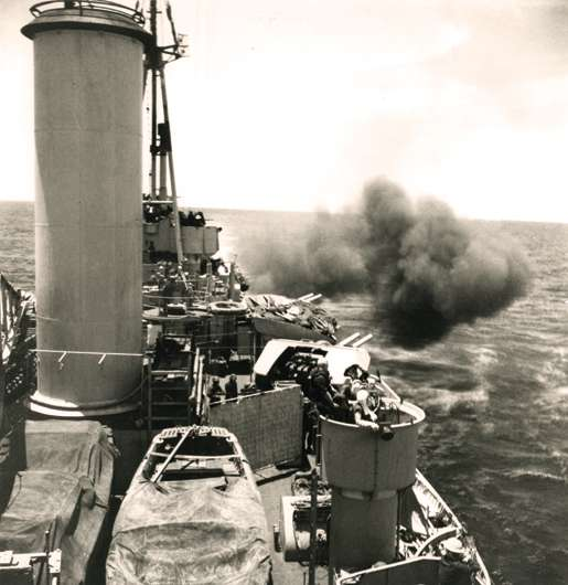 HMCS Uganda fires her guns on a Japanese airfield, May 1945. [PHOTO: GERALD MOSES, LIBRARY AND ARCHIVES CANADA—PA136073]