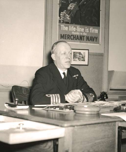 Capt. Eric S. Brand in front of a poster extolling the value of the merchant navy. [PHOTO: LIBRARY AND ARCHIVES CANADA—PA204258]