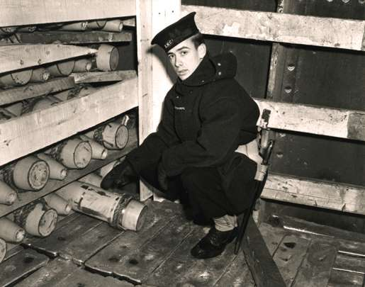 A rating of the Naval Control of Shipping Service inspects a cargo of shells aboard a wartime merchant ship at Halifax. [PHOTO: LIBRARY AND ARCHIVES CANADA—PA104377]