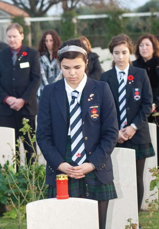 Students from CCI Renaissance School place candles on headstones. [PHOTO: TOM MacGREGOR]