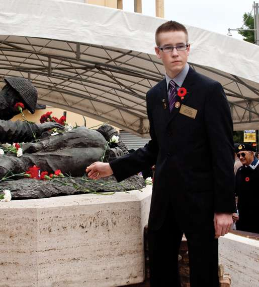 Youth representative Nolan Hill stands by the Price of Peace Monument. [PHOTO: TOM MacGREGOR]