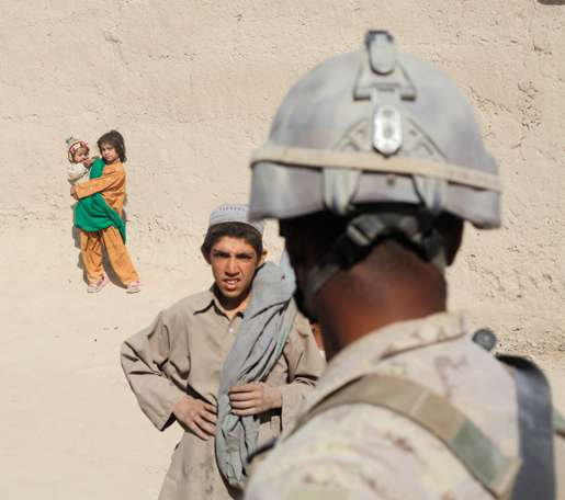 A young Afghan and a Canadian soldier appraise each other. [PHOTO: ADAM DAY]
