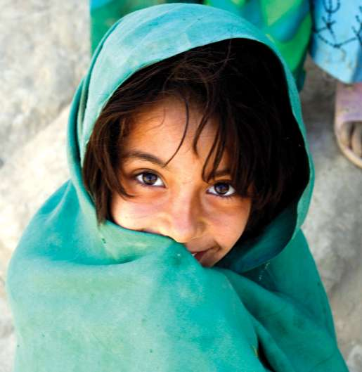 An Afghan girl smiles after receiving some Canadian candy. [PHOTO: ADAM DAY]