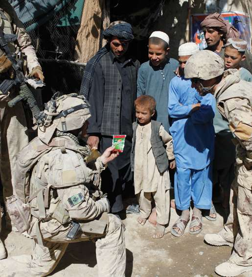 Sergeant Dwayne MacDougall speaking to children outside an Afghan shop. [PHOTO: ADAM DAY]