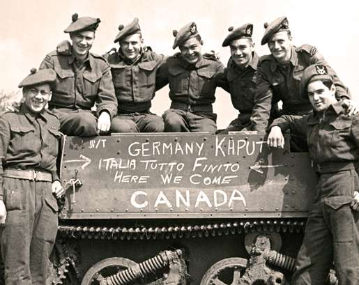 Smiles and a sign say it all following the end of hostilities in Europe. [PHOTO: LEGION MAGAZINE ARCHIVES]