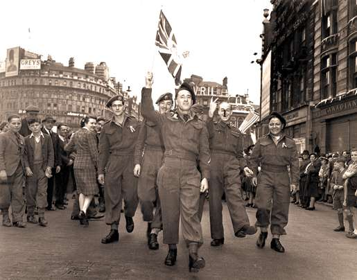Canadian soldiers celebrate the victory in London, England. [PHOTO: ERNEST J. DeGUIRE, LIBRARY AND ARCHIVES CANADA—PA176695]