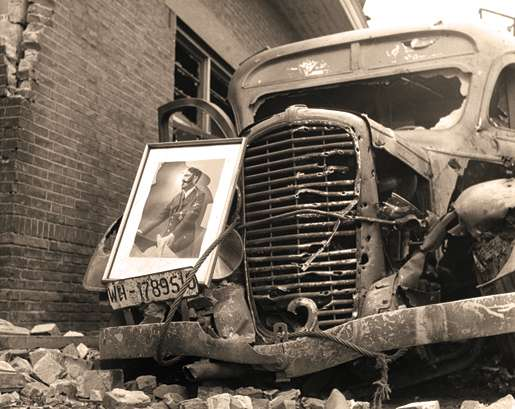A smashed portrait of Hitler leans against a destroyed German vehicle, May 1945. [PHOTO: LIBRARY AND ARCHIVES CANADA—PA130978]