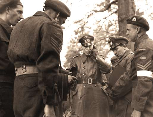 A German officer is linked up with Canadian and  German forces at Wageningen in the Netherlands. [PHOTO: ALEXANDER STIRTON, LIBRARY AND ARCHIVES CANADA—PA138588]