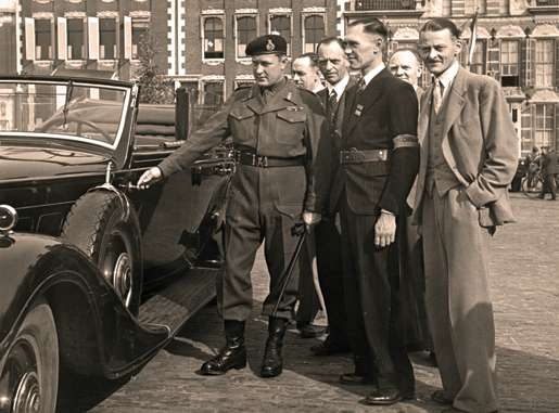 Dutch Resistance members and Canadian Maj.-Gen. B.M. Hoffmeister examine a captured German car, May 11, 1945. [PHOTO: G. FLEMING, LIBRARY AND ARCHIVES CANADA—PA138055]