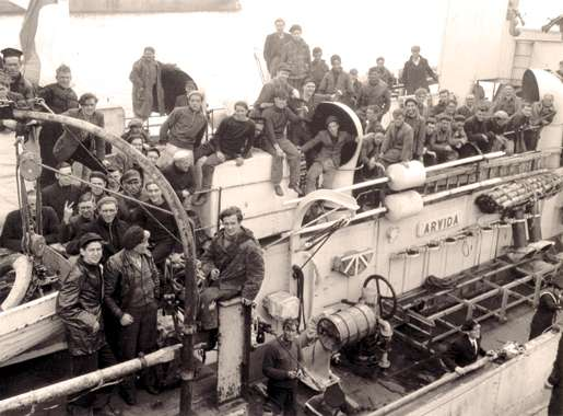 Survivors of a torpedoed merchant ship aboard HMCS Arvida at St. John's, September 1942. [PHOTO: GERALD M. MOSES, LIBRARY AND ARCHIVES—PA136285]